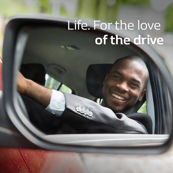 Man smiling at reflection in Renault KWID side mirror